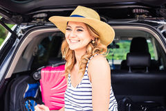 Pretty woman portrait at the car trunk with suitcases Royalty Free Stock Images