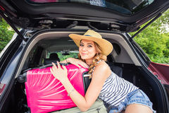Pretty woman portrait at the car trunk with suitcases Royalty Free Stock Image