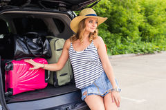 Pretty woman portrait at the car trunk with suitcases.  Royalty Free Stock Photography