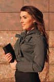 Pretty woman portrait near wall with notepad Stock Photos