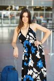 Pretty woman posing in the airport. Next to a suitcase dressed in a long dress stock images