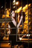 Pretty woman posing in cage outdoors at night Royalty Free Stock Image
