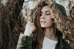 Pretty woman posing on camera in warm green jacket with fur hood. Very beautiful young woman with blonde hair, wide eyebrows and blue eyes looking sideways. Girl Stock Photos
