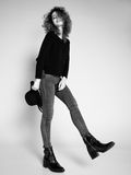 Pretty woman posing in denim pants and boots and black hat Royalty Free Stock Images
