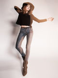 Pretty woman posing in denim pants and boots and black hat - intentional motion blur Stock Image