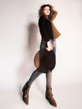 Pretty woman posing in denim pants and boots and black hat - intentional motion blur Royalty Free Stock Image
