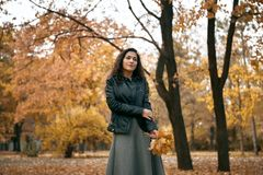Pretty woman posing with maple`s leaf in autumn park near big tree. Beautiful landscape at fall season royalty free stock photo