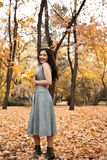 Pretty woman posing with maple`s leaf in autumn park near big tree. Beautiful landscape at fall season stock image