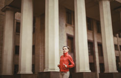 Pretty woman posing over big city background. Beautiful woman in a red jacket posing on a big city background royalty free stock images