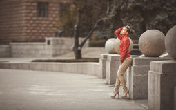 Pretty woman posing over big city background. Beautiful woman in a red jacket posing on a big city background stock photography