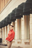 Pretty woman posing over big city background. Beautiful woman in a red jacket posing on a big city background stock photos