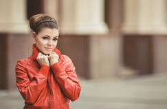 Pretty woman posing over big city background. Beautiful woman in a red jacket posing on a big city background royalty free stock photo
