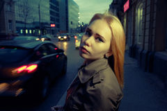 Pretty woman posing in pensive state of mind in the night street with blurred cars and streetlights on background, toned Royalty Free Stock Photo