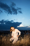 Pretty woman posing by sunset with dramatic sky behind Stock Photography