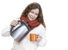 Pretty woman pouring hot water from the kettle into mug Royalty Free Stock Photography