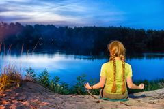 Pretty woman practicing yoga on the beach. Looking at sunset over river with blue night sky with stars Royalty Free Stock Image