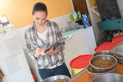 Pretty woman preparing bowls dog food at animal shelter Royalty Free Stock Photography