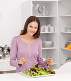 Pretty woman preparing a salad standing stock photos