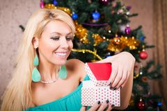 Pretty woman with present and Christmas tree Stock Photo