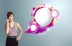 Pretty woman presenting abstract speech bubble copy space and ma. Pretty young woman presenting abstract speech bubble copy space and making phone call Stock Images