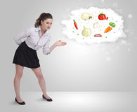 Pretty woman presenting a cloud of healthy nutritional vegetable Stock Photo
