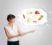 Pretty woman presenting a cloud of healthy nutritional vegetable Royalty Free Stock Photo