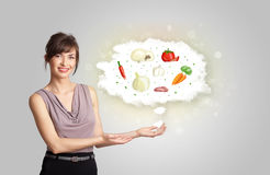 Pretty woman presenting a cloud of healthy nutritional vegetable Stock Image