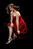 Pretty woman pulls down the hem of her dress. Isolated on a black background this beautiful young woman sitting on a footstool and wearing this beautiful red Royalty Free Stock Photo