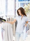 Pretty woman purchasing clothes. In shop, smiling Stock Image