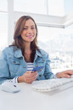 Pretty woman purchasing online with her credit card. In modern office Royalty Free Stock Images