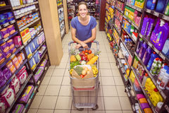 Pretty woman pushing trolley in aisle Stock Photography
