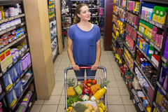 Pretty woman pushing trolley in aisle Stock Image