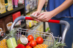 Pretty woman pushing trolley in aisle and texting Royalty Free Stock Photo