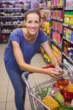 Pretty woman pushing trolley in aisle and texting Royalty Free Stock Images