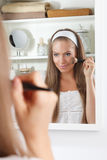 Pretty woman putting powder on the cheek Royalty Free Stock Photo