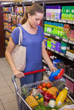 Pretty woman putting product in trolley Stock Photos