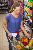 Pretty woman putting product in trolley Stock Photography