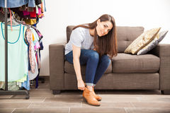 Pretty woman putting shoes on at home Royalty Free Stock Images