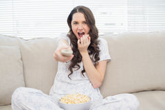 Pretty woman in pyjamas having popcorn while watching scary movi Royalty Free Stock Image