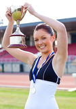 Pretty woman raising her trophy Royalty Free Stock Photo