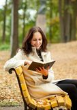 Pretty woman reading book on bench. Pretty woman reading book and smilling Stock Photo