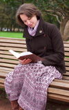 Pretty woman reading a book on a bench. In a park Stock Images