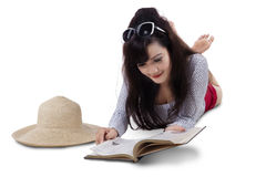Pretty woman reading book on the floor Stock Photos