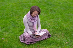Pretty woman reading a book on a grass Royalty Free Stock Photo