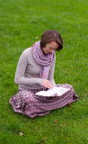 Pretty woman reading a book on a grass Royalty Free Stock Photography