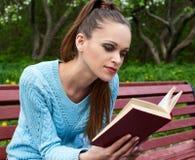 Pretty woman reading a book in the park. Pretty woman sitting on a bench in the park and reading a book Stock Photo