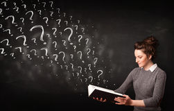 Pretty woman reading a book with question marks coming out from Stock Image
