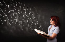 Pretty woman reading a book with question marks coming out from Stock Photos