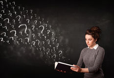 Pretty woman reading a book with question marks coming out from Royalty Free Stock Photos
