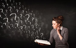 Pretty woman reading a book with question marks coming out from Royalty Free Stock Photography
